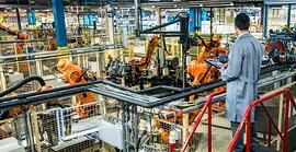Person with clipboard monitoring a factory with robots